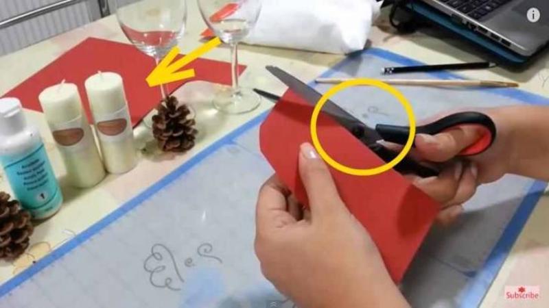 Taie o bucată de HARTIE roşie şi o aşează lângă cele 2 lumânări: Ce se întâmplă când pune mâna şi pe paharul de vin de lângă ele... nu pot să cred! Un ornament perfect pentru masa de Crăciun cu care vei da pe spate toţi invitaţii! WOW